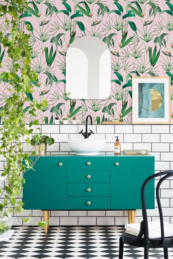 a bright bathroom with pink and green tropical wallpaper, an emerald vanity, cascading greenery and touches of gold