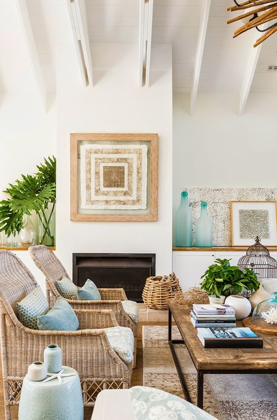 a bright beach and tropical living room with wicker chairs, a basket, aqua elements and pillows, bottles and catchy artworks