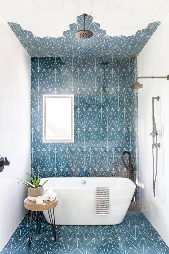 a bright beach bathroom with white and printed navy tiles, a bathtub, dark fixtures and a cork stool