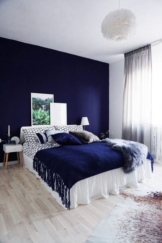 a bright bedroom with a navy accent wall, a white bed with printed blue bedding, simple nightstands and a fluffy pendant lamp