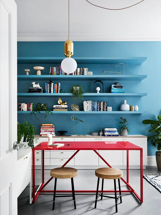 a bright blue contemporary home office with neutral storage units, floating shelves in blue and a hot red desk to contrast