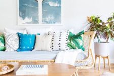 a bright coastal living room with a rattan sofa, colorful pillows, a woven rug and ottoman and a beach artwork