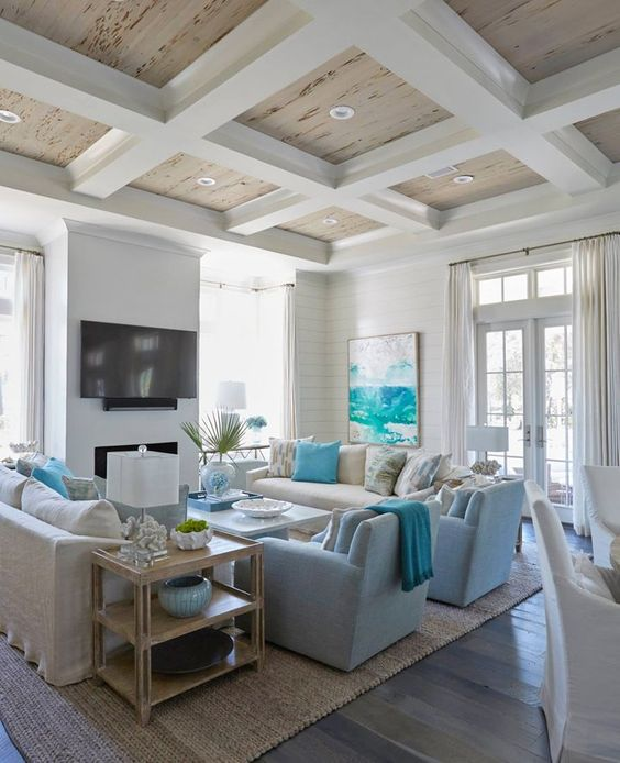 a bright coastal living room with white walls, neutral and light blue furniture, blue pillows, blankets and a turquoise artwork