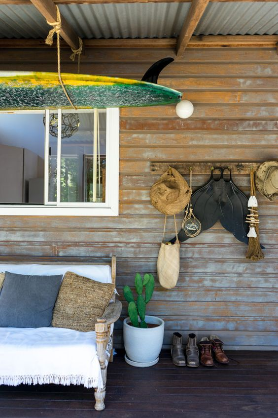 a bright coastal porch with a carved wooden sofa with woven bedding, a bright surf board suspended and some accessories hanging