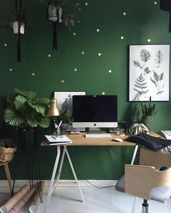 a bright green home office with a polka dot accent wall, stylish wooden furniture, potted plants here and there