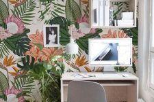 a bright home office nook with colorful tropical print wallpaper, minimal white furniture and potted greenery