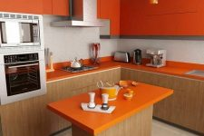 a bright minimalist kitchen with light stained wooden cabinets and a kitchen island, orange upper cabinets and countertops