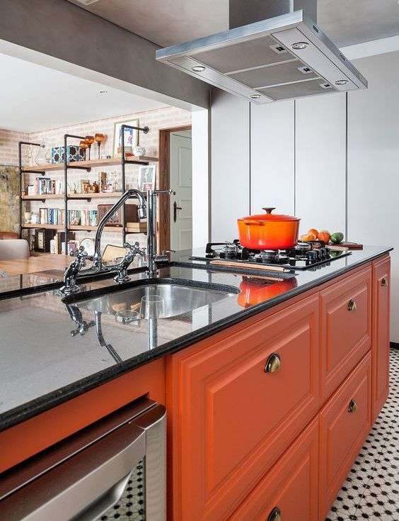 a bright modern kitchen with orange furniture, black stone countertops and a metal hood plus vintage fixtures
