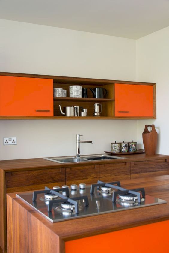 a bright modern kitchen with rich stained wooden cabinets and touches of bold orange is very spectacular