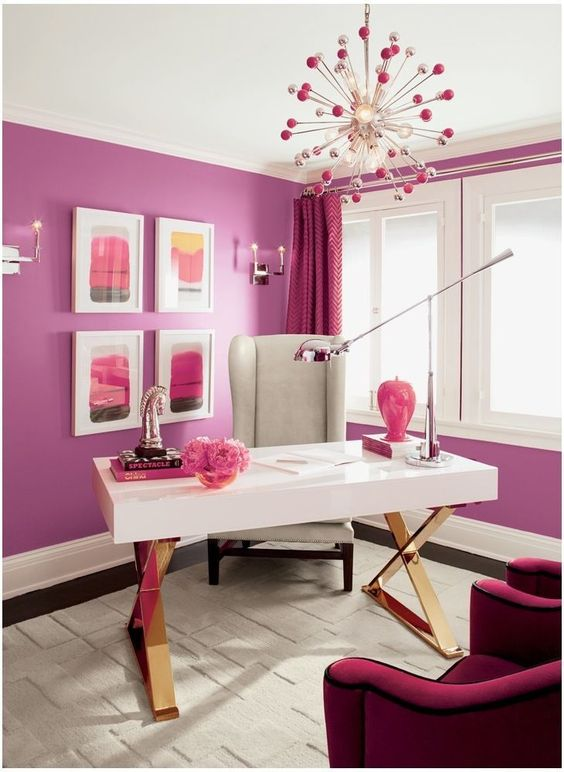 a bright purple and hot pink home office with purple walls, fuchsia curtrains, a quirky burst chandelier and fuchsia chairs