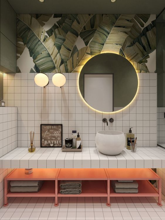 a bright tropical bathroom with banana leaf wallpaper, white tiles, a pink bench with storage and a lit up mirror