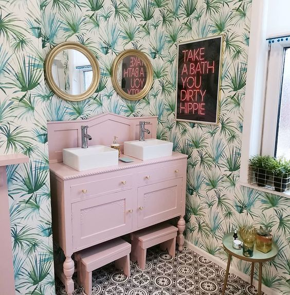 a bright tropical bathroom with tropical wallpaper, a blush vanity with stools, gold framed mirrors and a neon sign
