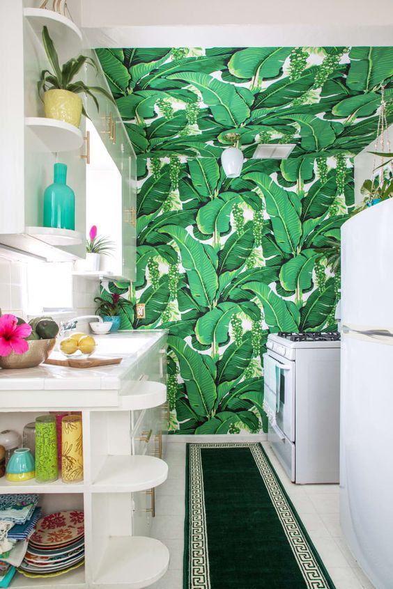 a bright tropical kitchen with a banana leaf wall and ceiling, white cabinets and bright tableware for fun