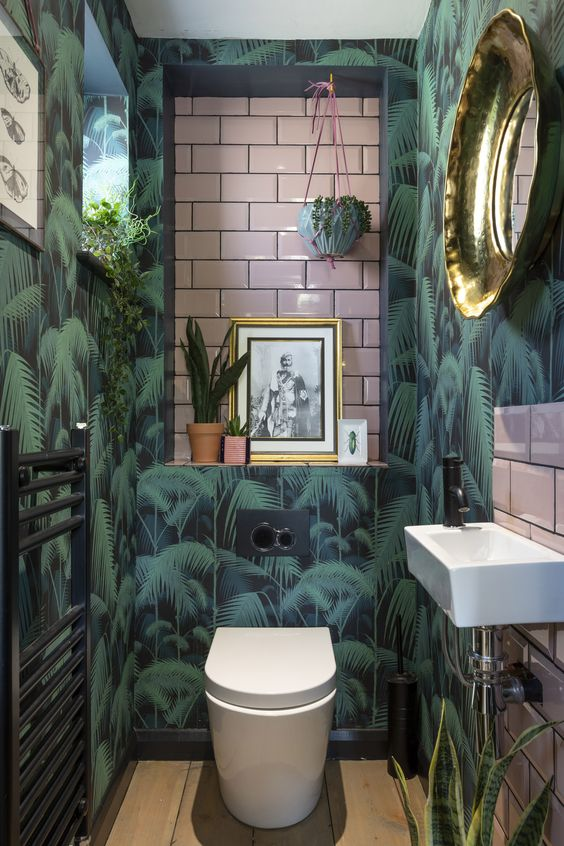 a bright tropical powder room with tropical wallpaper, pink tiles, potted greenery and touches of gold