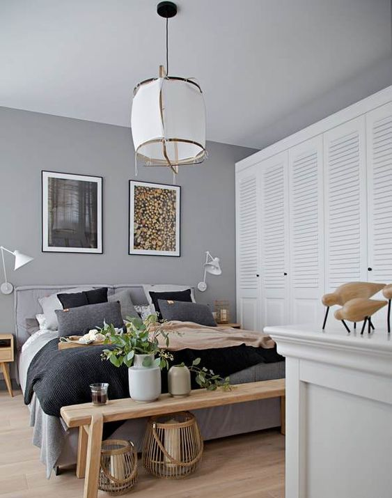 a catchy grey bedroom with wooden furniture, grey and black bedding, greenery, candle lanterns and cool art