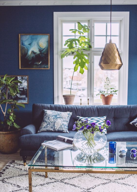 a catchy living room with navy walls, a dark blue sofa, potted plants, copper and brass touches