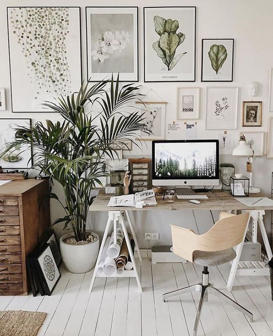 a catchy neutral home office with a large gallery wall, modern and vintage furniture, potted plants and lots of accessories