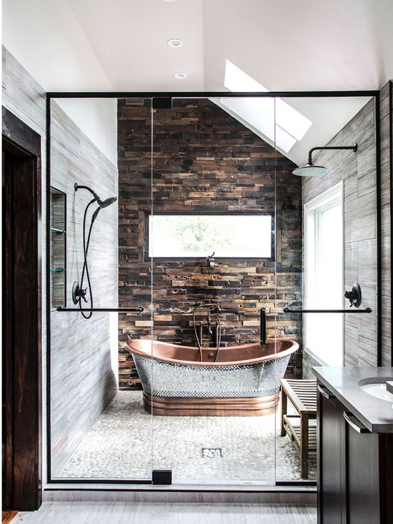 a chalet bathroom clad with stone and stone-like tiles, a catchy copper bathtub that accents the space