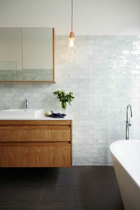 a charming coastal bathroom clad with very pale green glazed tiles, a tub, a wooden vanity and a pendant lamp