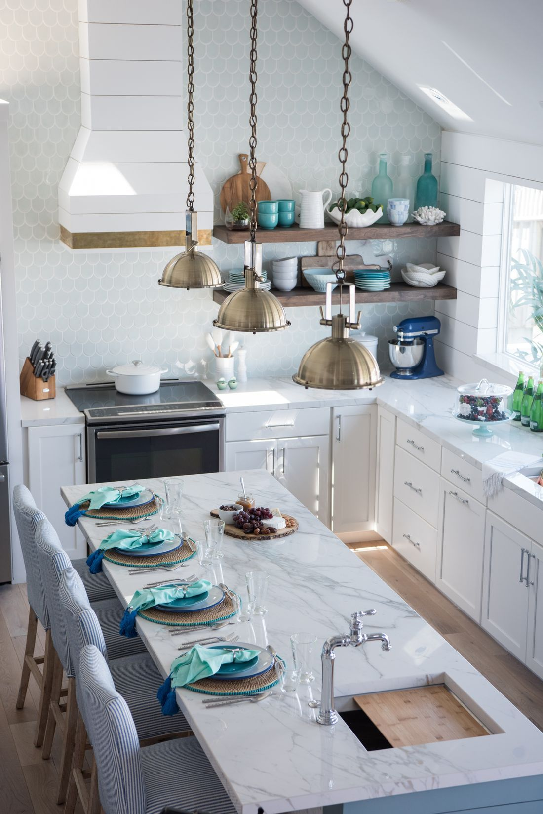 a charming coastal kitchen with white cabients, an aqua scale tile backsplash, a marble kitchen island and blue striped chairs