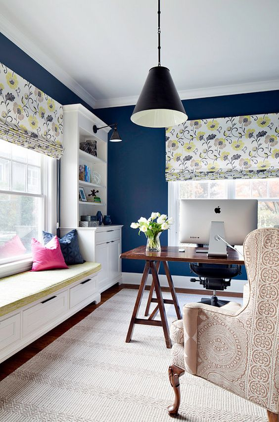 a cheerful navy home office with a trestle desk, floral shades and a printed chair, bright pillows and a mattress