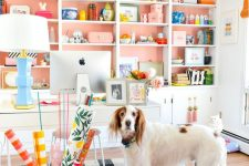 a cheerful pink home office with a storage unit that takes the whole wall, white furniture and bright accessories