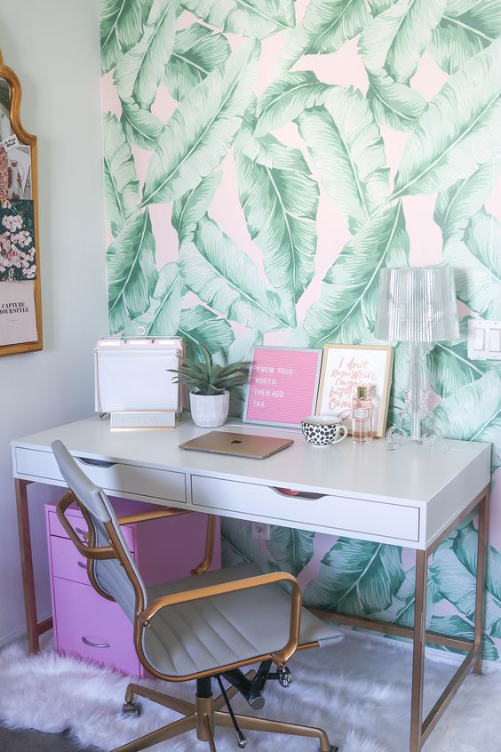 a cheerful tropical home office with a banan leaf wall, a hot pink cabinet, touches of gold for a shiny touch
