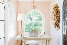 a chic and glam peachy pink home office nook with refined furniture, a crystal chandelier and a statement artwork on the wall