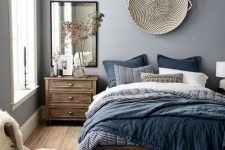 a chic blue bedroom with stained wooden furniture, a woven basket on the wall, blue bedding, a mirror, a boho rug and some faux fur
