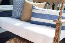 a chic coastal front porch with a hanging upholstered daybed with blue pillows and a wicker ottoman plus potted plants