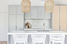 a chic coastal kitchen featuring light grey cabinetry and a matching kitchen island, a glossy tile backsplash and woven lamps