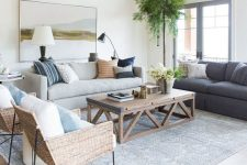 a chic coastal living room with two sofas, wicker chairs, a wooden table, printed pillows and potted greenery