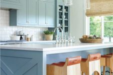 a chic coastal space with light blue cabinets, a blue kitchen island, glass pendant lamps and wood and leather stools