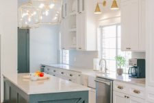 a chic farmhouse coastal kitchen with white cabinets, a teal kitchen island, gold pendant lamps and sconces