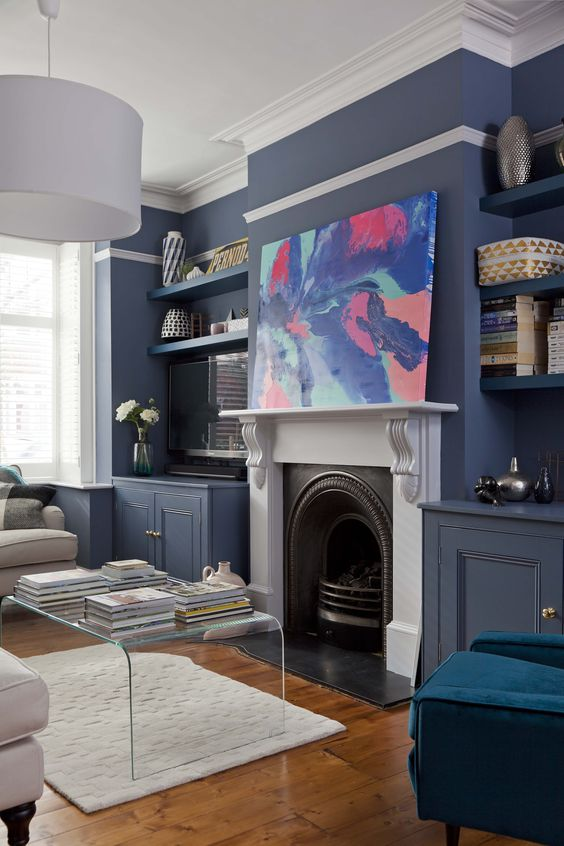 a chic living room with navy walls, a classic blue chair, a bright artwork and an acrylic coffee table looks stylish