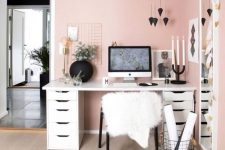 a chic modern pink home office with light pink walls, a tall mirror, a comfy desk, black pendants and other touches for chic