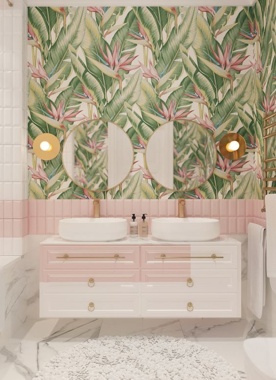 a chic tropical bathroom with pink and white tiles, tropical wallpaper, a floating color block vanity and touches of gold