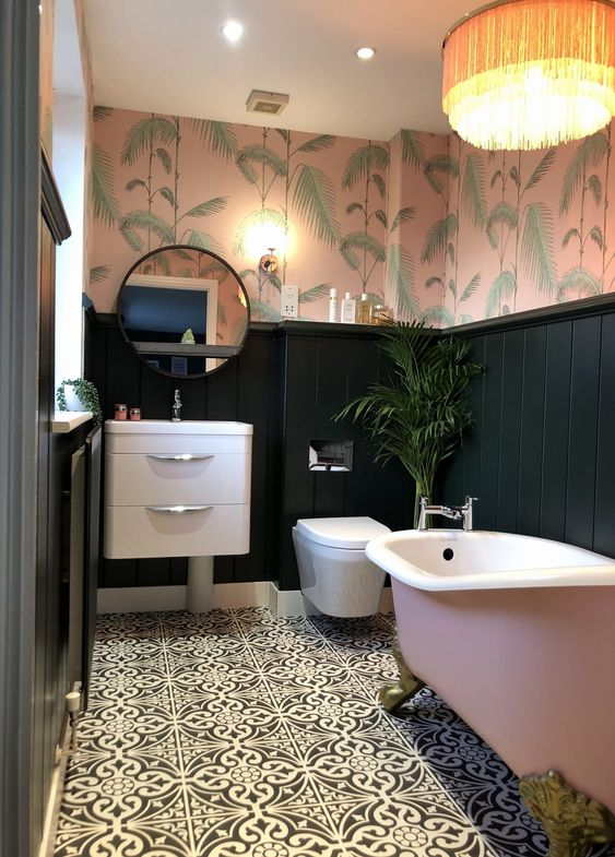 a chic tropical bathroom with tropical wallpaper, black panels, a pink tub, a floating vanity and a lamp with fringe