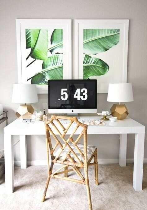 a chic tropical home office nook with a rattan chair, tropical artworks and gold faceted lamps