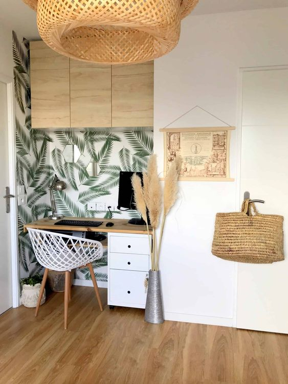 a chic tropical home office nook with neutral furniture, a tropical leaf wall, a woven lamp and pampas grass