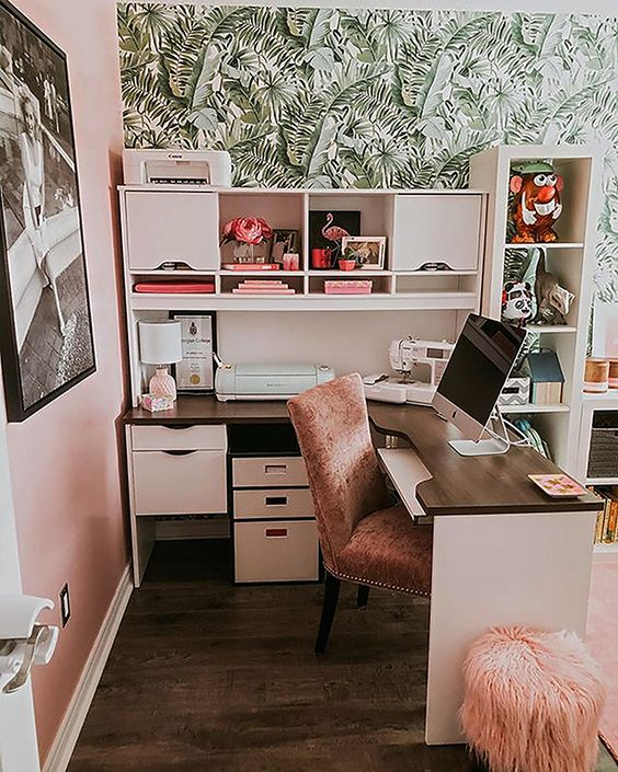 a chic tropical home office with a banana leaf wall, white furniture, pink chairs and accessories for a glam feel