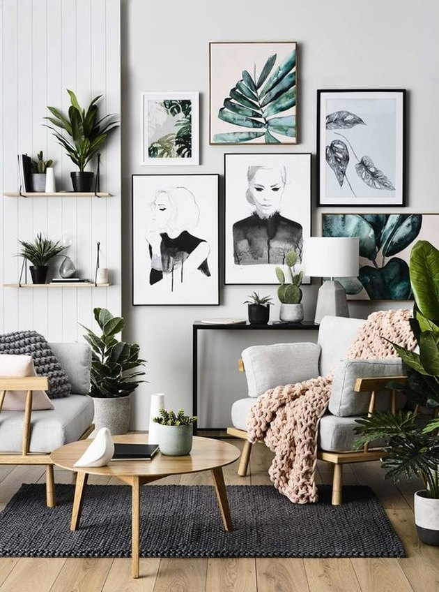 a chic tropical living room with white beadboard walls, neutral furniture, a large tropical gallery wall and potted plants