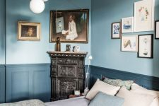 a chic vintage-inspired bedroom with light blue walls, navy paneling, a ceiling with molding, a bubble chandelider and a vintage hearth