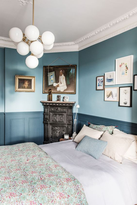 a chic vintage inspired bedroom with light blue walls, navy paneling, a ceiling with molding, a bubble chandelider and a vintage hearth