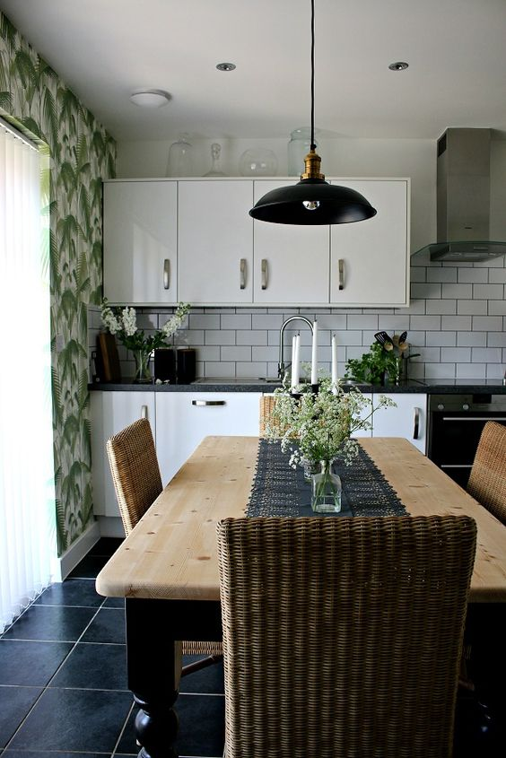 a chic vintage-inspired kitchen with tropical wallpaper, white cabinets and subway tiles, wooden furniture and woven chairs