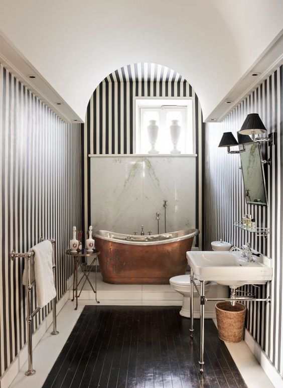 a chic vintage-inspired monochromatic bathroom with a copper bathtub that adds warmth and color to the space