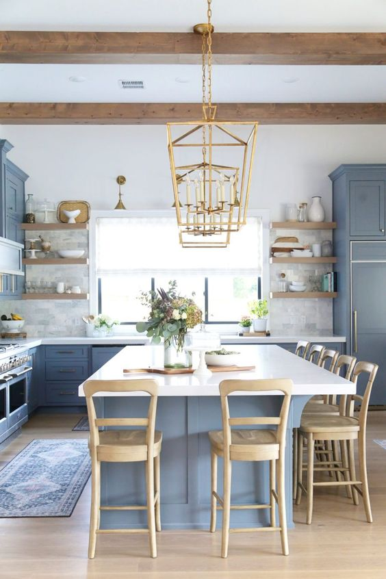 a coastal farmhouse kitchen with classic blue cabinetry and a kitchen island, wooden stools, beams and shelving and touches of gold