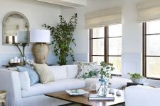 a coastal farmhouse living room in white, with light blue paneling, a chandelier, potted greenery, candles and tan ottomans