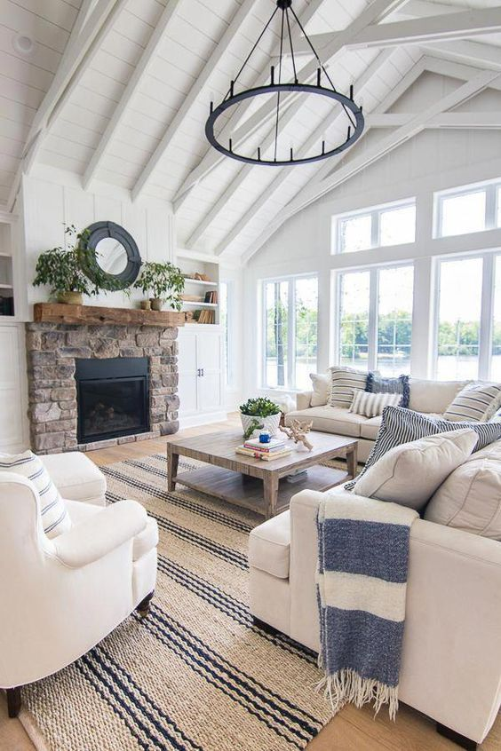 a coastal farmhouse living room in white, with tan and creamy furniture, printed pillows, a brick clad fireplace, a chandelier and a striped rug