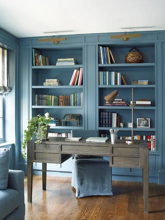 a coastal home office in light blue, with built in storage units, a weathered wood desk and touches of brass here and there